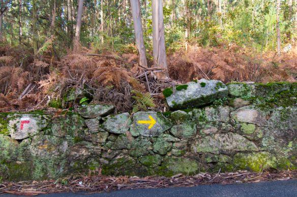 yellow arrow on stone wall