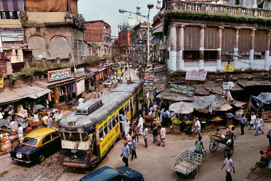 """Tram, Calcutta, India, 1996; A Tram, Calcutta, India, 1996 MCS1996002 K010 Magnum Photos, NYC5923 """"For McCurry, Calcutta is the most visual city on the planet, spinning with chaos and clutter, crumbling under the weight of its overpopulation, utterly out of control, yet vital and alive. Vendors spill into streets, which hold a confusion of cars, trams, rickshaws, bicycles and pedestrians. So how to make this picture? McCurry looked for an office or apartment on a second floor of a street corner. 'And that is the wonder of the place. Twenty minutes later, I am on a bed in a couple's apartment, making the picture and staying on for a cup of tea."""" Anthony Bannon. (2005). Steve McCurry. New York: Phaidon Press Inc., 37. National Geographic, March 1997, India: Fifty Years of Independence Phaidon, 55, South Southeast, Iconic Images, final book_iconic, iconic photographs final print_HERMITAGE Dirty, hot, smoggy, friendly- that's how one resident describes Calcutta, a city so humid even the buildings seem to sweat. With crowded streets pockmarked with potholes, an unreliable phone system, and a long love affair with Marxism, Calcutta is only now trying to lure foreign investors. National Geographic, Jeffrey C. Ward (May 1997). India: Fifty years of Independence. National Geographic, vol. 191(5) A tram winds its way through the streets of Calcutta. Dirty, hot, smoggy, friendly, it is a place so humid that even the buildings seem to sweat. This Calcutta street is a cacophony of visual noise. McCurry spent a long time searching for a way to capture the energy and vitality of this most unique of cities. His response was to find a vantage point above street level. Fortunately, he was welcomed into an apartment on the street corner by a young couple. After taking this image he stayed for a cup of tea. South Southeast_Book Steve Mccurry_Book Iconic_Book final print_Sao Paulo final print_Birmingham final print_HERMITAGE retoucher_Sonny Fabbri 3/24/2015"""